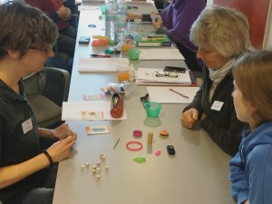 Three individuals, deep in conversation, during a PORTL game at a shaping workshop in Germany